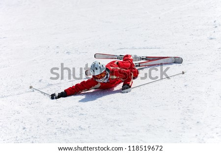 Female skier after falling down on a mountain slope - stock photo