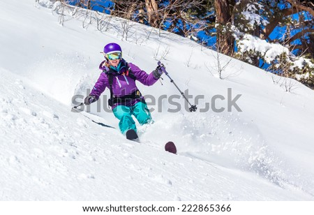 Skier in deep snow off piste skiing in soft snow on a cold sunny day