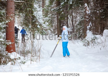 Female skier looking back when skiing in winter forest - stock photo