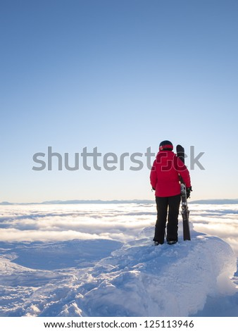 Female skier looking out over cloud covered valley in Åre, Sweden.