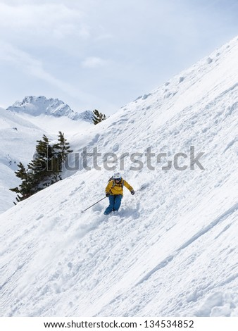 Female skier making turn on steep slope in powder snow with mountains in the background.