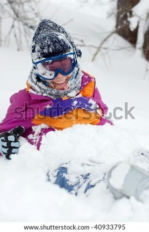 Female skier sitting in the deep snow, smiling - stock photo