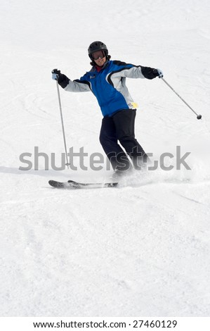 Female skier skiing on ski trail, leaving behind cloud of powder snow when skid stopping - stock photo