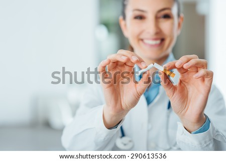 Female smiling doctor breaking a cigarette, stop smoking and prevention concept - stock photo