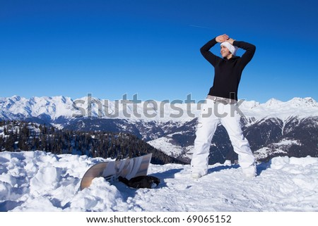 Female snowboarder is standing over cliff in Dolomites - stock photo