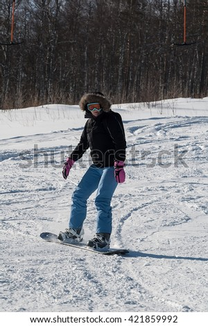 Female snowboarder on the slopes on sunny day