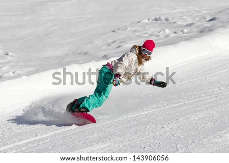 Female snowboarder rocking the slopes on a sunny morning in the Italian alps - stock photo