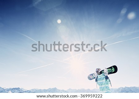 Female snowboarder wearing colorful helmet, blue jacket and grey gloves standing with snowboard in her hands and preparing for ride - snowboarding concept - stock photo