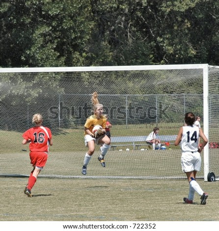 Female soccer goal keeper jumps to save a goal - stock photo
