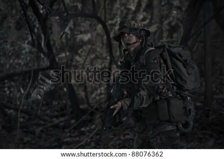 female soldier operating in the darkness of jungle - night operation - stock photo