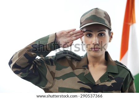 Female soldier saluting with Indian flag in background - stock photo