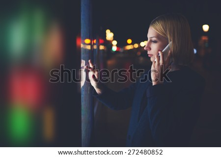 Female speaking on mobile phone while using automated teller machine with big digital screen while standing in night city with out-of-focus lights,woman verifies account balance on banking application - stock photo