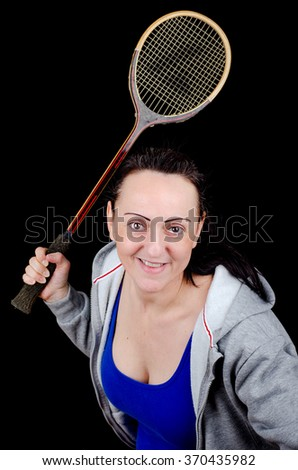 Female squash player swinging racket in training. Portrait with black background.