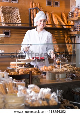 Female staff selling fresh pastry and baguettes in local bakery - stock photo
