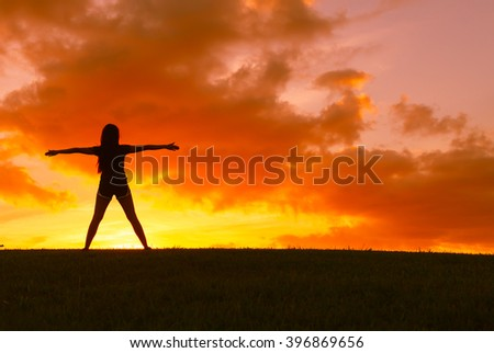 Female stretching her arms facing a beautiful sunset.   - stock photo