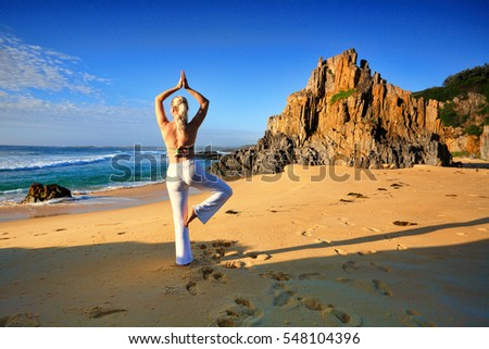 Female stretching on one leg yoga tree pose vrksasana by the beach early morning