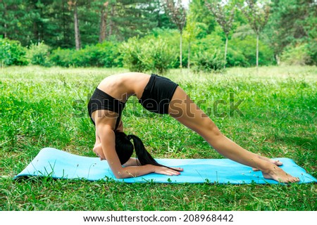 female stretching outdoor in the city park, fitness and yoga exercises - stock photo