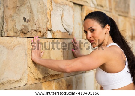 Female strong athlete pushing wall for stretching calves. Fit woman on urban workout looking confident at camera.