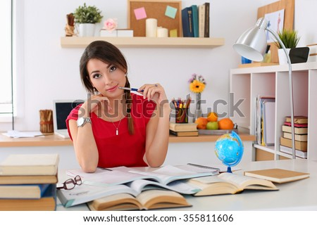 Female student at workplace with pile of textbooks portrait holding pen studying. Woman writing letter, list, plan, making notes, doing homework. Education, self development and perfection concept - stock photo