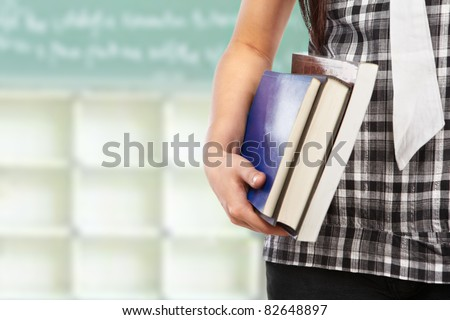 Female student body part holding book in the classroom - stock photo