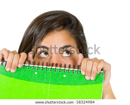 female student covering her face with a notebook isolated over white - stock photo