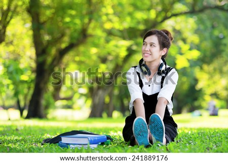 Female student girl outside in park listening to music on headphones while studying - stock photo