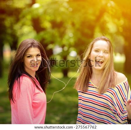 Female student girls outside in park listening to music on headphones - stock photo
