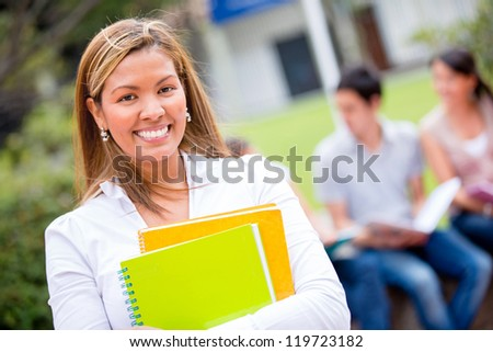 Female student holding notebooks and looking very happy - stock photo