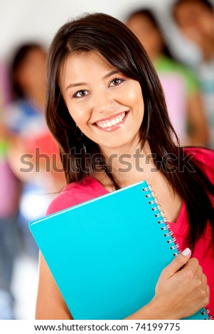 Female student holding notebooks with a group behind - stock photo