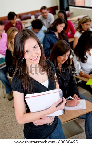 Female student in the classroom with a notebook and smiling - stock photo