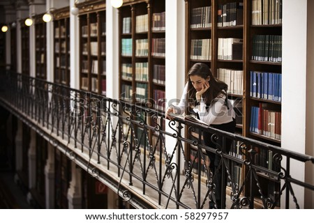Female student leaning at handrail in old library reading a book; bookshelf with old books collection in background. - stock photo