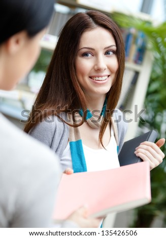 Female student offers a book to her friend at the library - stock photo