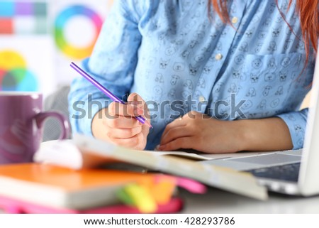 Female student or designer at workplace holding pencil and writing or making sketches. Woman writing letter, list, plan, making notes, doing homework. Education or creative work concept - stock photo