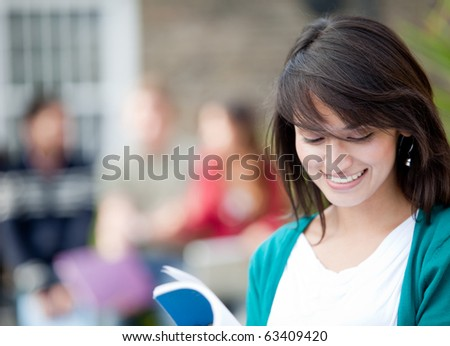 Female student outdoors with a group of people at the background - stock photo