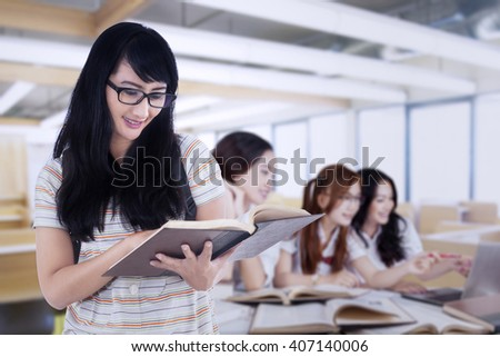 Female student reading a book in the classroom while her friends discussing together - stock photo