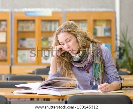 female student reads the book in library