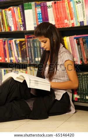 Female student selecting book from library - stock photo