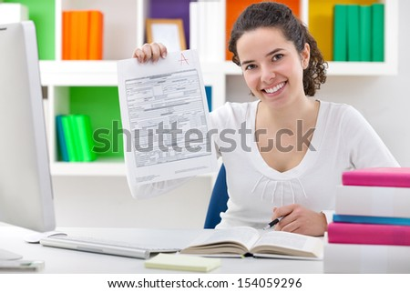 Female student showing perfect grade A plus, grade / test results. - stock photo