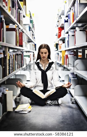 Female student sitting in Yoga pose in between bookshelves in modern university library and meditating over a book. - stock photo