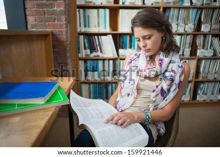 Female student sitting on chair and reading a book in the library - stock photo