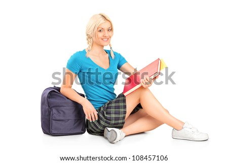 Female student sitting on floor, isolated on white background