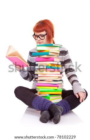 female student sitting with pile of books and reading book - stock photo