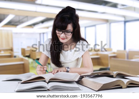 Female student studying at reading room while writing the source on book - stock photo