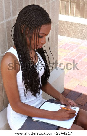 Female student taking notes at a college campus - stock photo