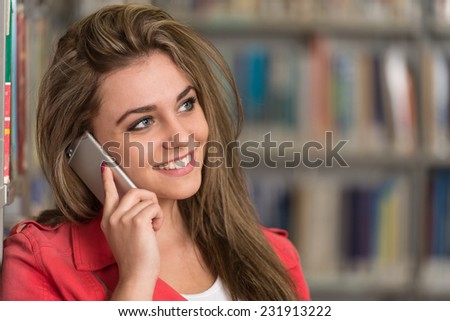 Female Student Talking On The Phone In Library - Shallow Depth Of Field - stock photo