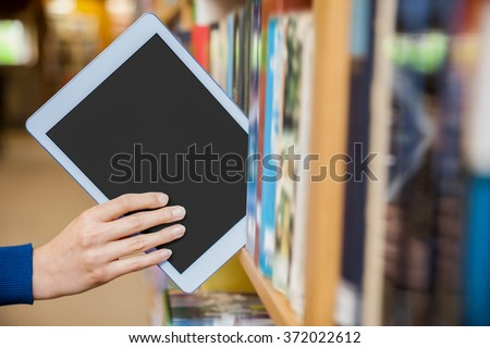 Female student tidying a tablet in a bookshelf in the library at the university - stock photo