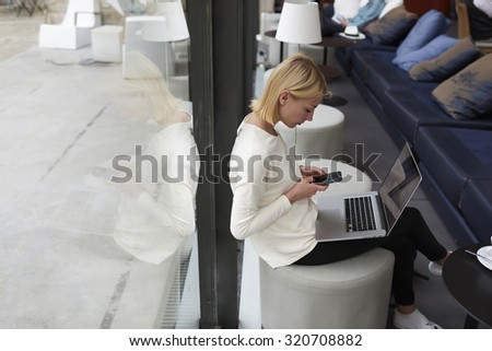 Female student typing text message on smart phone sitting at library with laptop computer, freelancer woman working on net-book in modern coffee shop interior, young businesswoman at coffee break  - stock photo