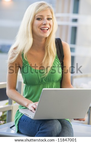 Female student using computer outside - stock photo