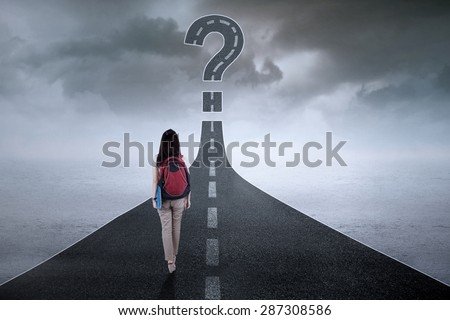 Female student walking on the street while carrying backpack with a question mark on the end - stock photo