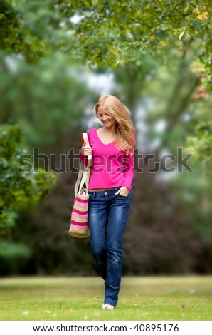 Female student walking through the campus smiling - stock photo